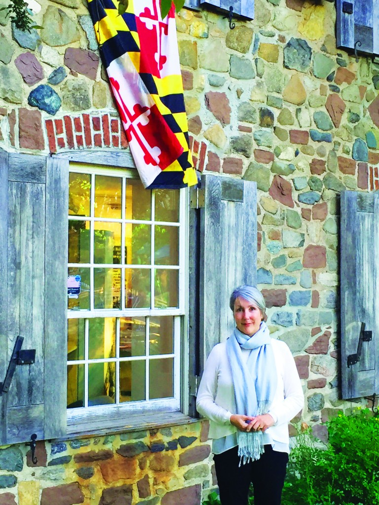 Maier in front of the Old Stone House, which proudly displays a Maryland flag. Credit: Mirielle Clifford